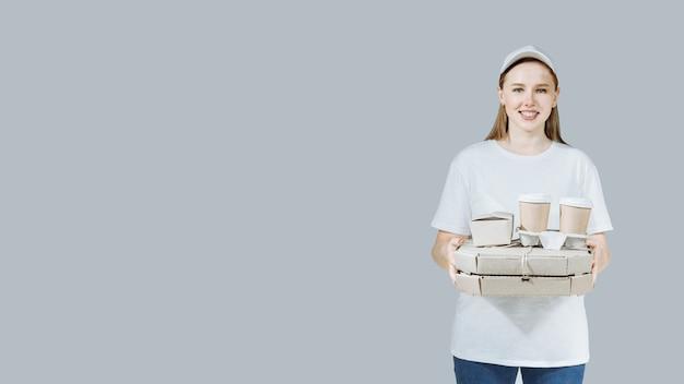 Voedselbezorgingsdienst vrouw werknemer met dozen pizza, koffie en fastfoot. glimlachend koeriersmeisje. . bezorgservice vanuit winkel- of restaurantconcept.