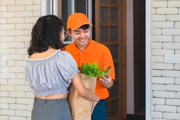 Voedselbezorgservice man vers voedsel overhandigen aan ontvangende jonge vrouw klant