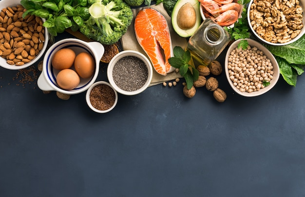 Voedselbronnen van omega 3 en gezonde vetten op donker bovenaanzicht.