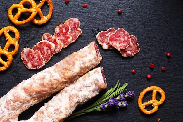 Voedselconcept biologische franse salami saucisson op zwarte leisteen bord met kopieerruimte