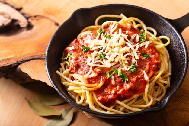Voedselconcept eigengemaakte spaghetti bolognese in ijzer dat op houten achtergrond met exemplaarruimte wordt gegoten
