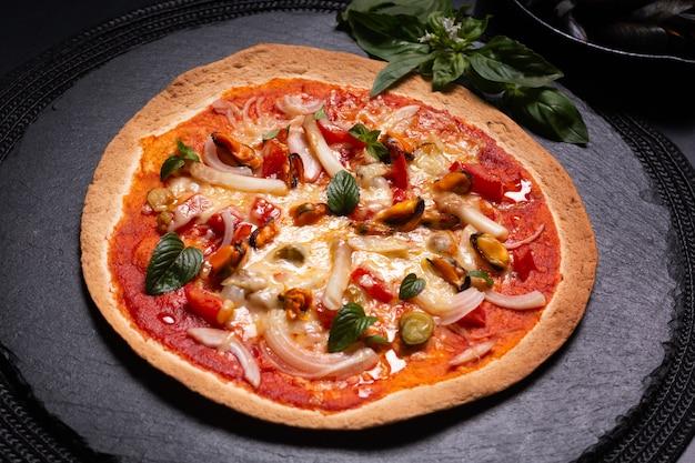 Voedselconcept eigengemaakte tortilla zeevruchtenpizza op zwarte leisteenplaat