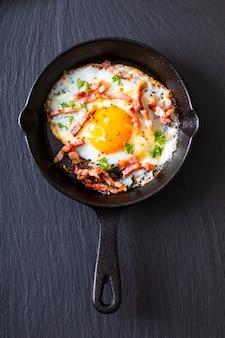 Voedselconcept gebraden ei en kaasbacon in gietijzerkoekepan met exemplaarruimte