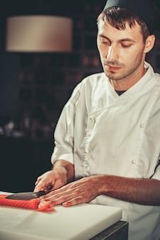 Voedselconcept jonge chef-kok in witte uniform gesneden zalmvis op tafel in restaurant waar hij werkt
