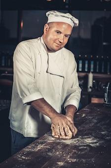 Voedselconcept. jonge vrolijke chef-kok in wit uniform en hoed kneed het deeg op de houten tafel in het interieur van de moderne restaurantkeuken. traditionele italiaanse pizza bereiden