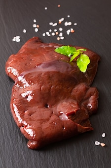 Voedselconcept organische verse plak ruwe rundvleeslever op zwarte leiraad
