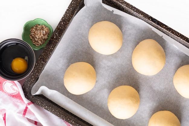 Voedselconcept rijzen, rijzen van gistdeeg van hamburgerbroodjes in bakpan vóór het bakken