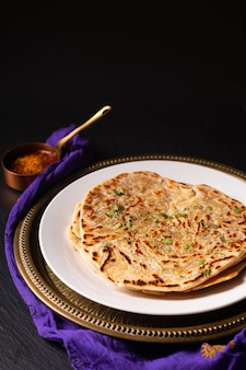 Voedselconcept spot focus zelfgemaakte paratha, parotta of porotta gelaagde flatbread op zwarte achtergrond