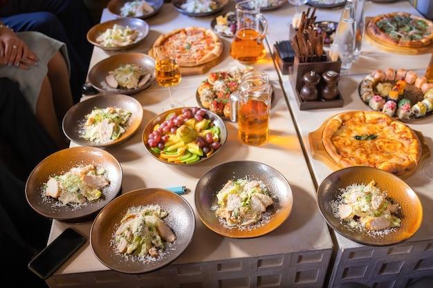 Voedselconcept, tafel met verschillende snacks erop. salade met zalm, caesar skuric, ingemaakte champignons, brood.