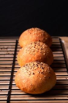 Voedselconcept vers gebakken zelfgemaakte hamburgerbroodjes op zwarte achtergrond met exemplaarruimte
