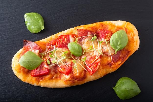 Voedselconcept zelfgemaakte biologische pizza met tomaat, basilicum en ham met kopie ruimte