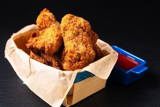 Voedselconcept zelfgemaakte kruiden crispy fried chicken tenders in houten dienblad met kopieerruimte