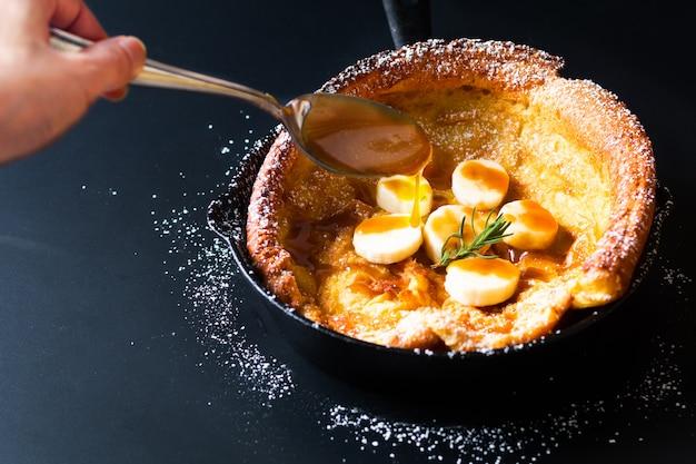 Voedselconcept zelfgemaakte nederlandse baby of duitse banaan caramel topping pannenkoek in koekepan ijzer gegoten op zwart