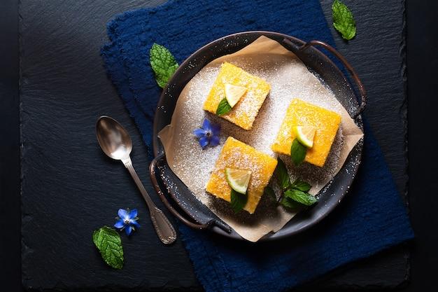 Voedselconcept zelfgemaakte rustieke lemon bar pie op zwarte achtergrond met kopie ruimte