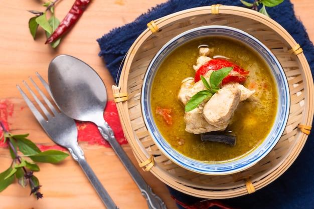 Voedselconcept zelfgemaakte thaise kip groene curry op een houten bord met kopieerruimte