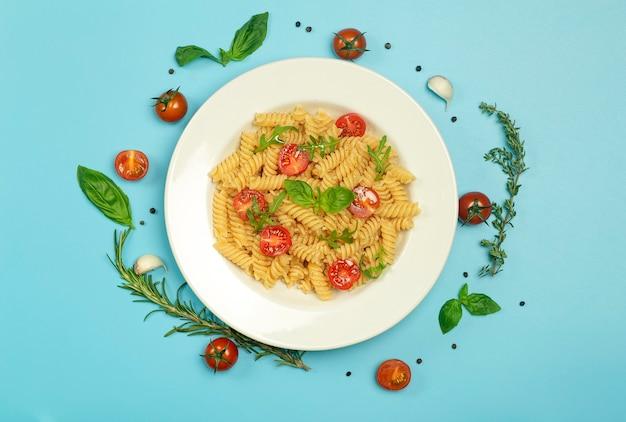 Voedseldeegwaren op een blauwe achtergrond. italiaanse fusilli pasta met tomaten, kruiden en basilicum op een witte plaat.
