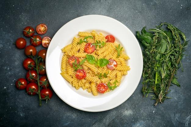 Voedseldeegwaren op een donkere achtergrond. italiaanse fusilli pasta met tomaten, kruiden en basilicum op een witte plaat.