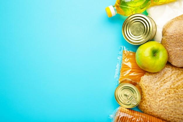 Voedseldonaties voor mensen. schenkingsvoedsel op de blauwe achtergrond. bovenaanzicht.