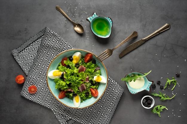 Voedselfotografie van bovenaf. samenstelling van rucola salade, tomaten, vlees gestoomde eieren, olijven in een blauwe schotel op de achtergrond van een betonnen tafel. lifestyle foto.