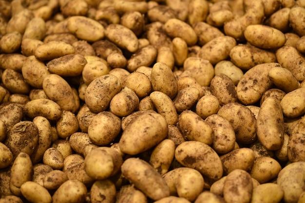 Voedselgroenten verse nieuwe aardappels, achtergrond. aardappelspatroon voor verkoop in markt