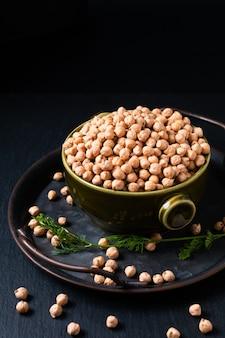 Voedselingrediëntconcept rew kikkererwten in groene kom met zwarte achtergrond met exemplaarruimte