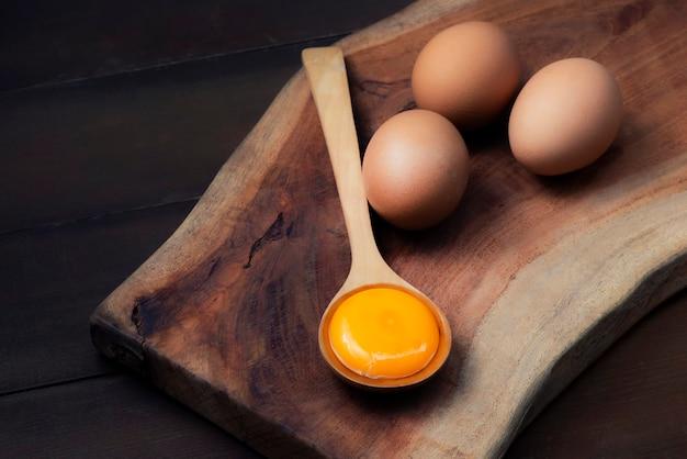 Voedselingrediënten (eierdooiers) voor het serveren op een lepel, houten vloer en rauwe eieren op hout achtergrond