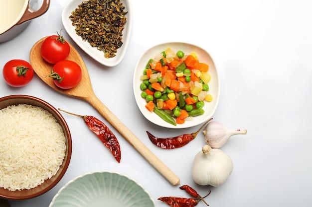 Voedselingrediënten en keukengerei voor het koken op wit wordt geïsoleerd