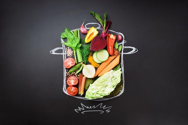 Voedselingrediënten voor het mengen van romige soep op geschilderde stoofpot over zwart bord.