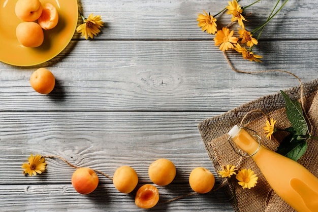 Voedselkader met abrikozen, een fles sap en gele bloemen op een houten achtergrond met exemplaarruimte