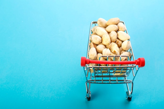 Voedselkar gevuld met pistachenoten in schelpen op een blauwe ondergrond