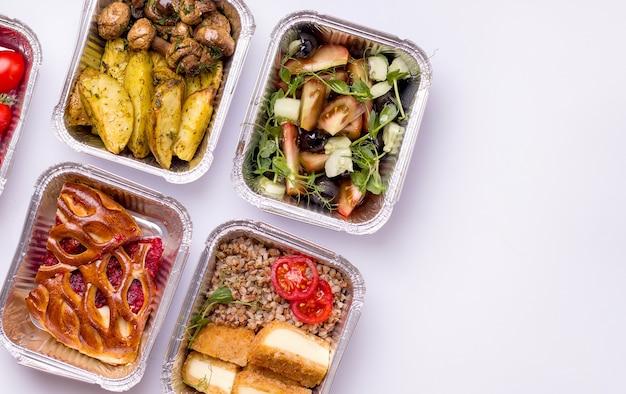 Voedsellevering. gerechten voor dinerpap, salade, aardappelen met champignons.