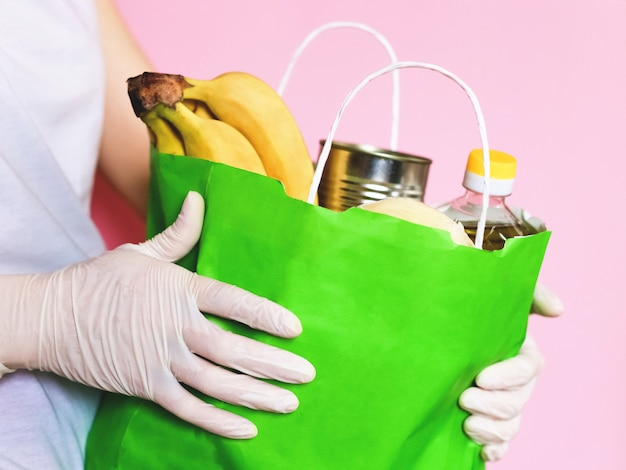 Voedsellevering. handen in handschoenen. coronavirus. papieren zak met voedsel