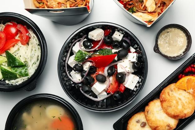 Voedsellevering. het voedsel haalt binnen dozen op witte achtergrond weg