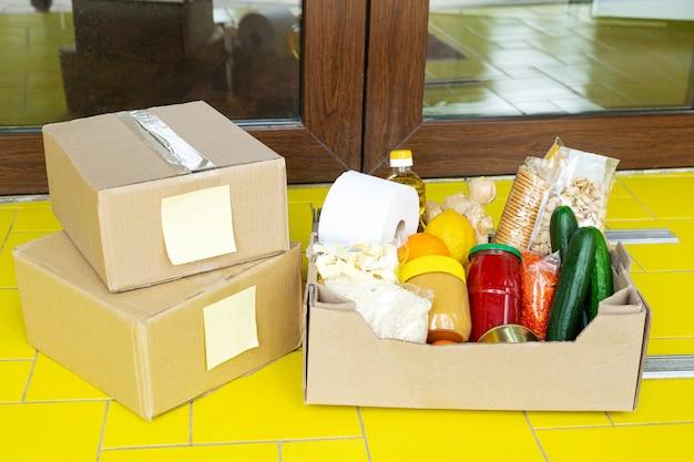 Voedsellevering. levering van voedselbakken op de drempel bij de deur van het huis. contactloze sociale thuisbezorging, veilig winkelen