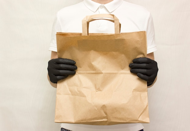 Voedsellevering. man koerier met voedselpakket