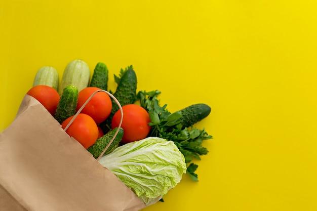Voedsellevering. papieren zak met groenten op een gele achtergrond.