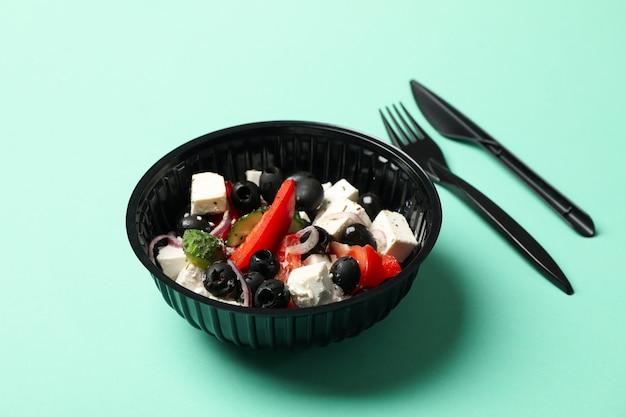 Voedsellevering. salade in meeneemdoos op muntachtergrond