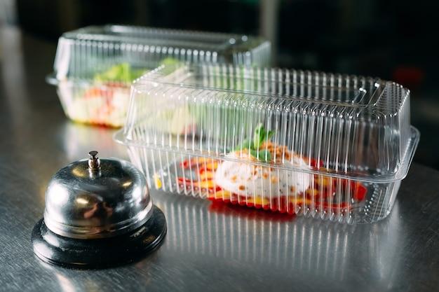 Voedsellevering. verdeeltafel in een restaurant met een metalen bel. voedsel in plastic bakjes. panna cotta en groentesalade in plastic wegwerpcontainers.