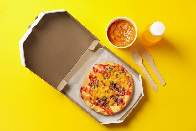 Voedsellevering. voedsel in afhaaldozen op gele achtergrond