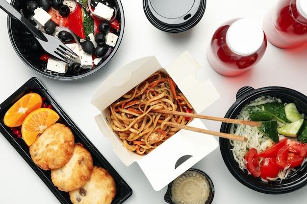 Voedsellevering. voedsel in afhaalmaaltijden dozen op witte muur