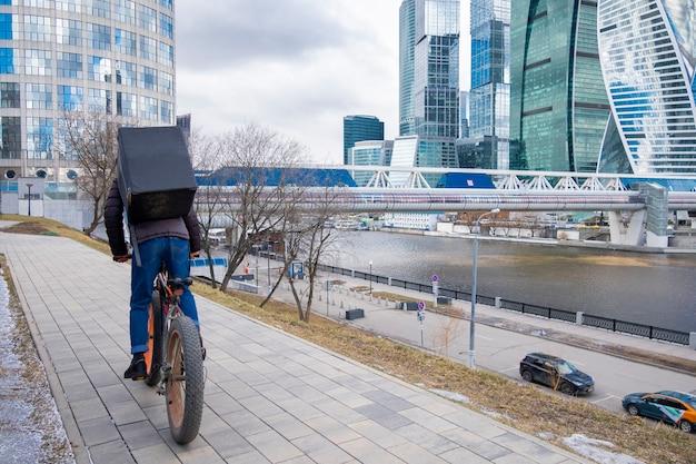 Voedselleveringsbedrijf per koerier op de fiets in de buurt van zakencentrum moskou