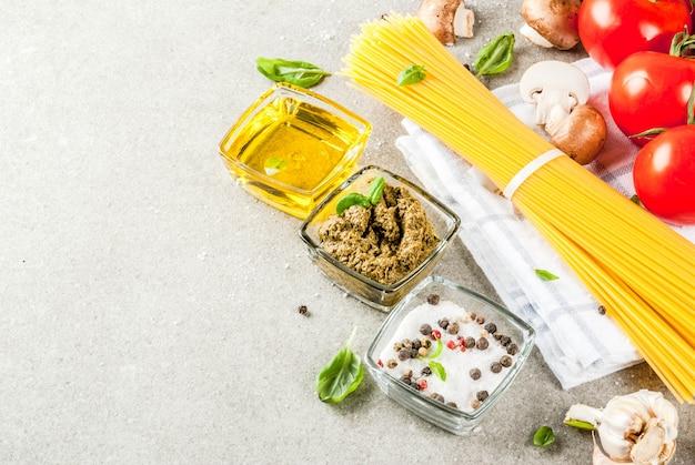 Voedseloppervlak, ingrediënten voor het koken van het diner. pasta spaghetti, groenten, sauzen en kruiden, grijze stenen oppervlak bovenaanzicht