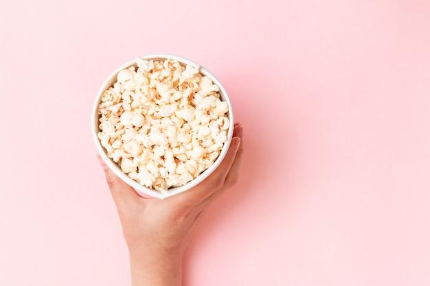 Voedselsamenstelling van de popcorn van de handholding in emmer op de roze ruimte van het achtergrond hoogste meningsexemplaar