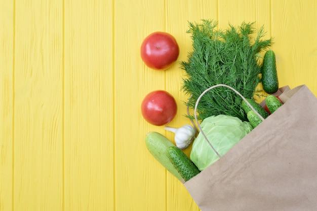Voedselschenkingspakket groenten om de armen te helpen op een gele houten muur met plaats voor uw tekst