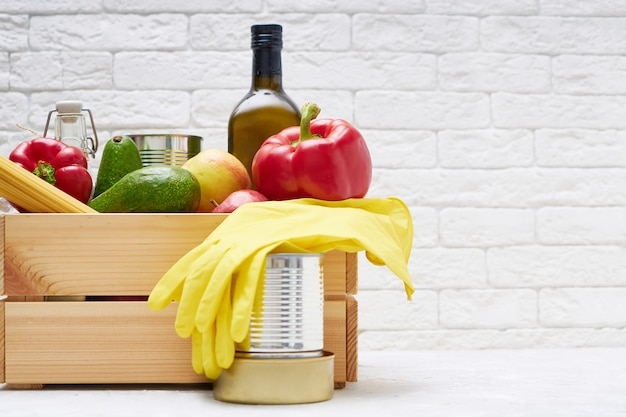 Voedselvoorraden in een houten doos. groenten, fruit, ingeblikt voedsel, pasta. donatie, voedselbezorging, coronavirus