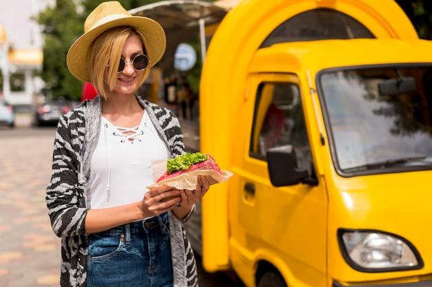 Voedselvrachtwagen en vrouw die een sandwich houden