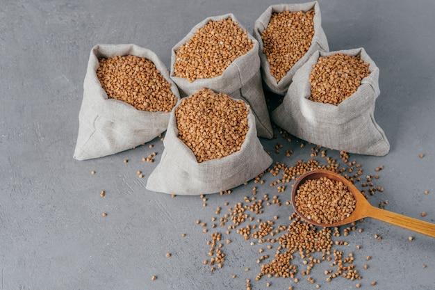 Voedzaam ingrediënt dat vitamines bevat. ontsproten van linnenzakken met boekweit tegen grijze achtergrond. biologisch voedsel. gezonde voeding