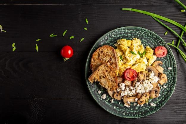 Voedzaam roerei met champignons, ui en tomaten als ontbijt. plaats voor tekst, bovenaanzicht.