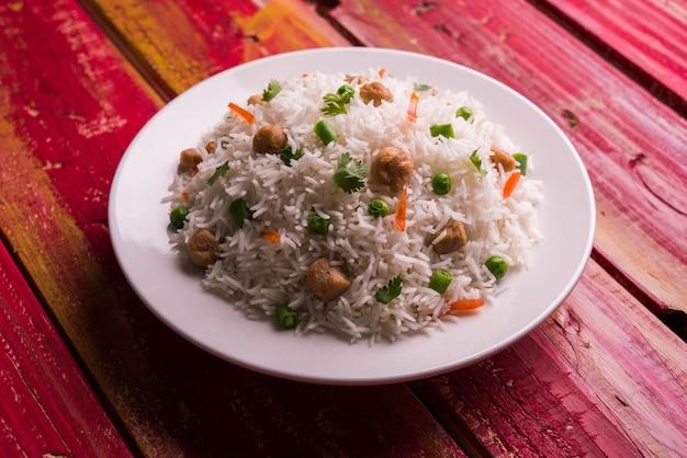 Voedzame sojabonenpulao of pilaf of sojabrok gebakken rijst met doperwtjes en bonen. geserveerd in een kom over kleurrijke of houten achtergrond. selectieve focus