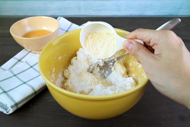 Voeg met de hand parmezaanse kaas toe aan het deeg in de mengkom voor het bakken van braziliaans kaasbrood